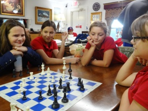 Mary Alice, Caty, Rylee and Diana prepare for chess match.