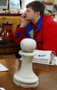 Cole contemplates his next move with the only chess piece left on the table.